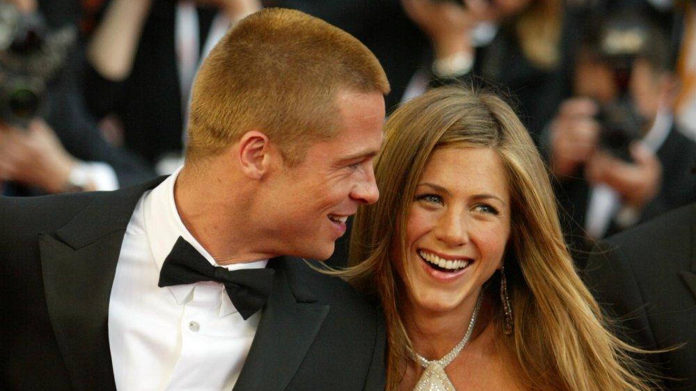 Brad Pitt et Jennifer Aniston se tenant la main et riant de la première troy en 2004