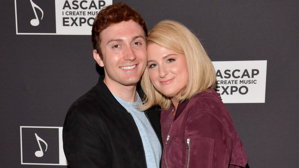 Daryl Sabra and Meghan Trainor hugging on the red carpet