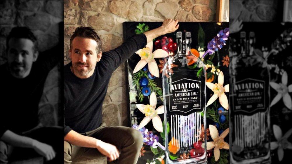 Ryan Reynolds posant avec une peinture d'une bouteille de gin Aviation