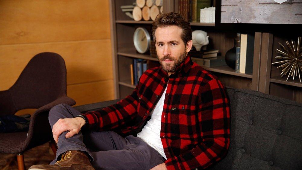 Un Ryan Reynolds barbu assis avec sa jambe croisée, vêtu d'un plaid