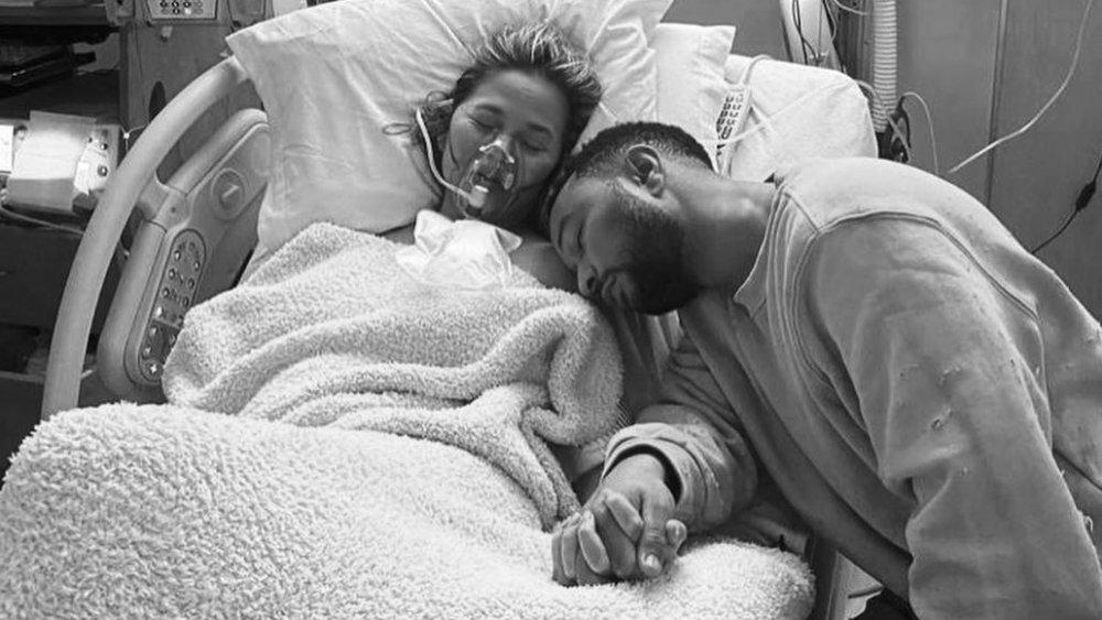 Chrissy Teigen et John Legend se tenant la main et se reposant dans sa chambre d'hôpital