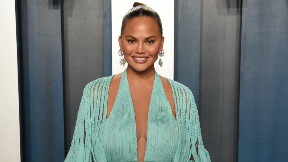 Chrissy Teigen sourit en posant dans une robe bleu clair à la Vanity Fair Oscar Party 2020