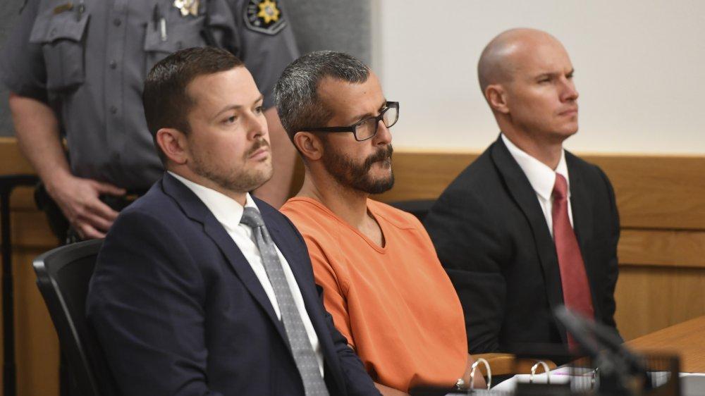 Chris Watts dans une combinaison orange, assis avec ses avocats lors de son procès en 2018