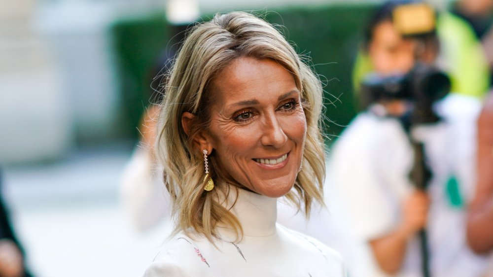 Céline Dion smiling in white turtleneck top