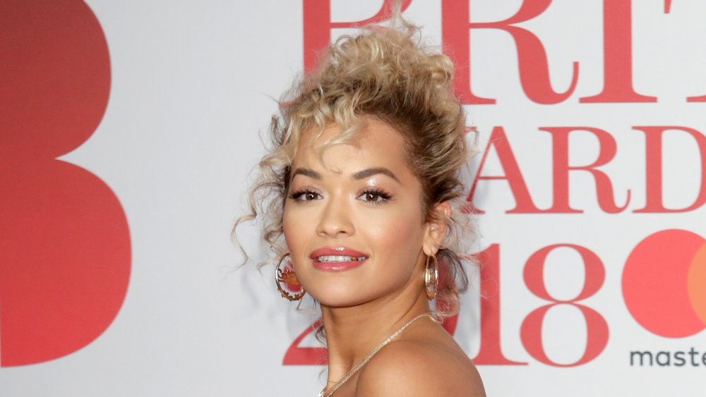 Rita Ora with hair done up and gold earrings