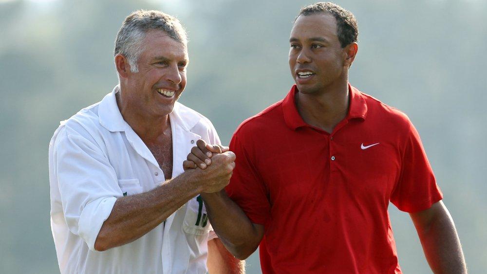 Steve Williams et Tiger Woods se serrant la main et souriant sur le terrain de golf