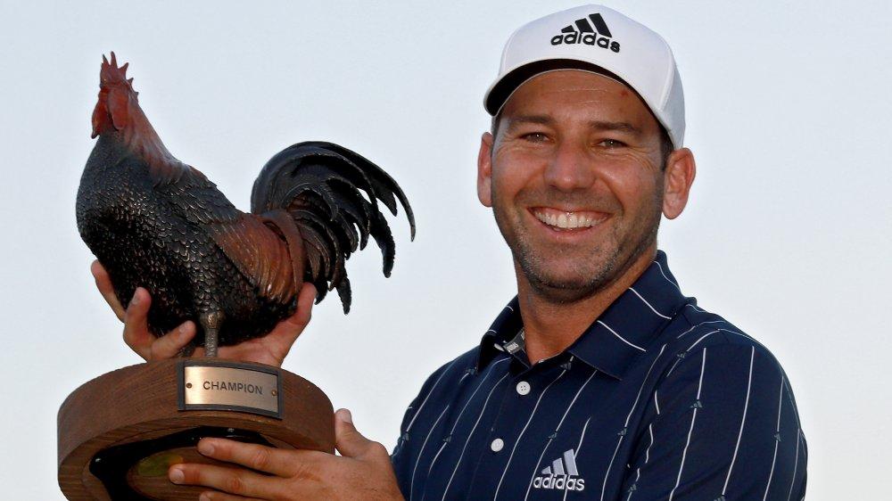 Sergia Garcia souriant et tenant un trophée de poulet