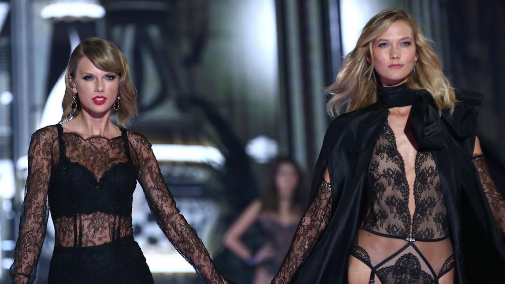 Taylor Swift et Karlie Kloss marchent côte à côte sur une scène en se tenant la main