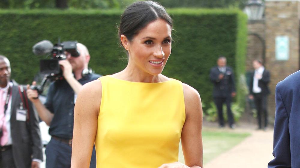 Meghan Markle marchant en robe jaune