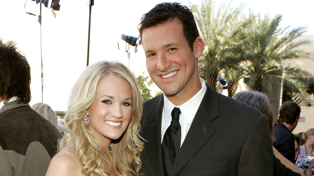 Tony Romo et Carrie Underwood posant sur un tapis rouge