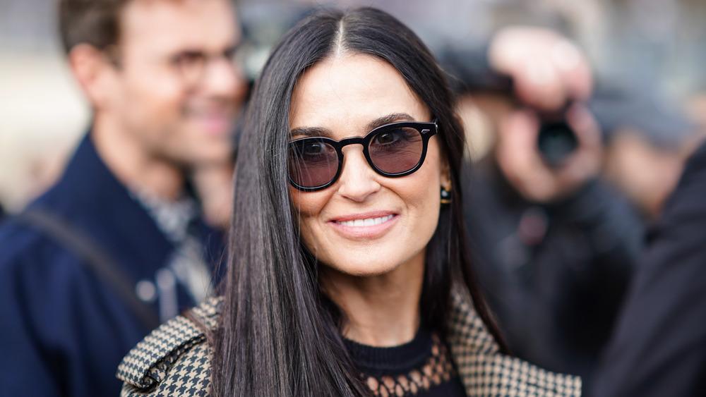 Demi Moore porte des lunettes de soleil marron et sourit à la caméra lors d'un événement