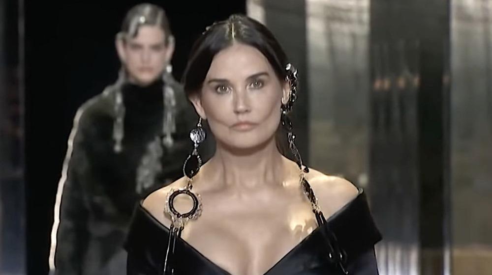 Demi Moore portant des boucles d'oreilles pendantes noires se promène dans un défilé Fendi