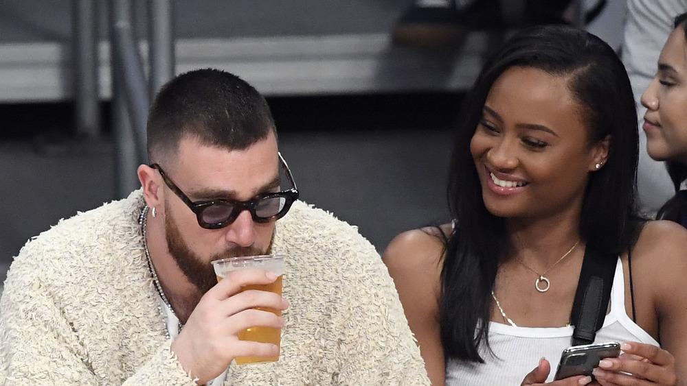 Travis Kelce, buvant une bière, côté court lors d'un match de la NBA, portant des lunettes de soleil;  Kayla Nicole, cheveux longs baissés, souriant à Travis Kelce, débardeur blanc, côté court au match de basket