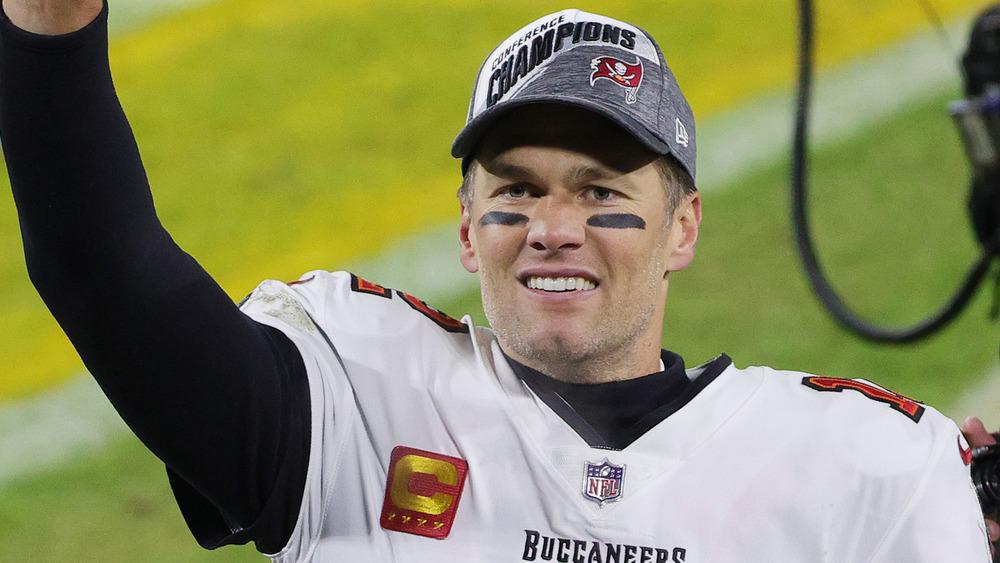 Tom Brady souriant avec bras levé sur un terrain de football