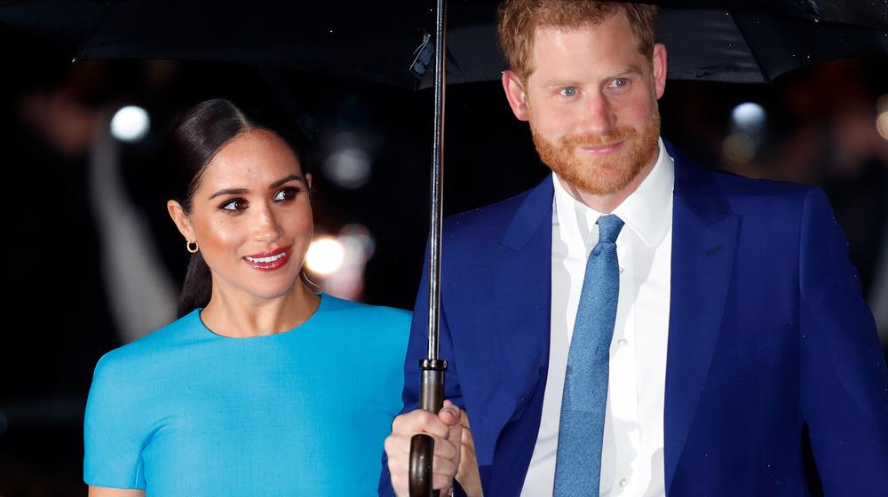 Meghan Markle et le prince Harry se tiennent sous un parapluie lors d'un événement