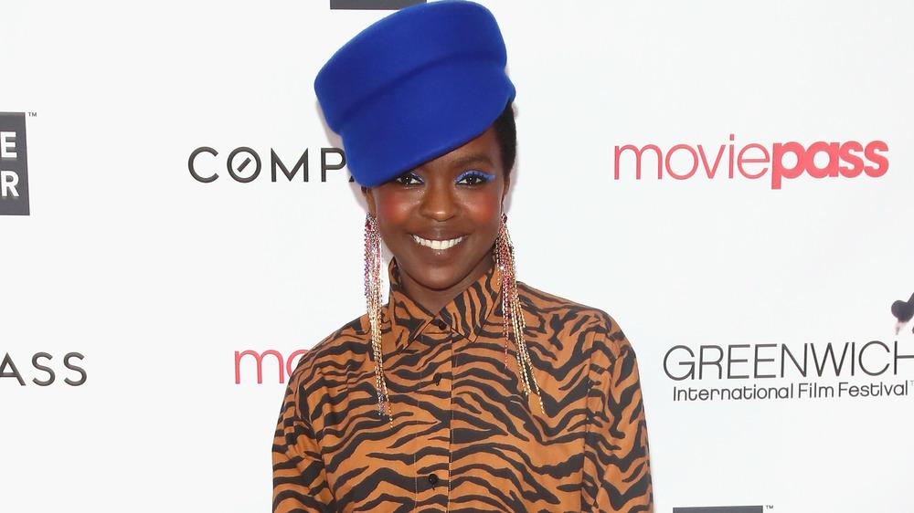 Lauryn Hill souriant dans un chapeau bleu et un chemisier à imprimé tigre