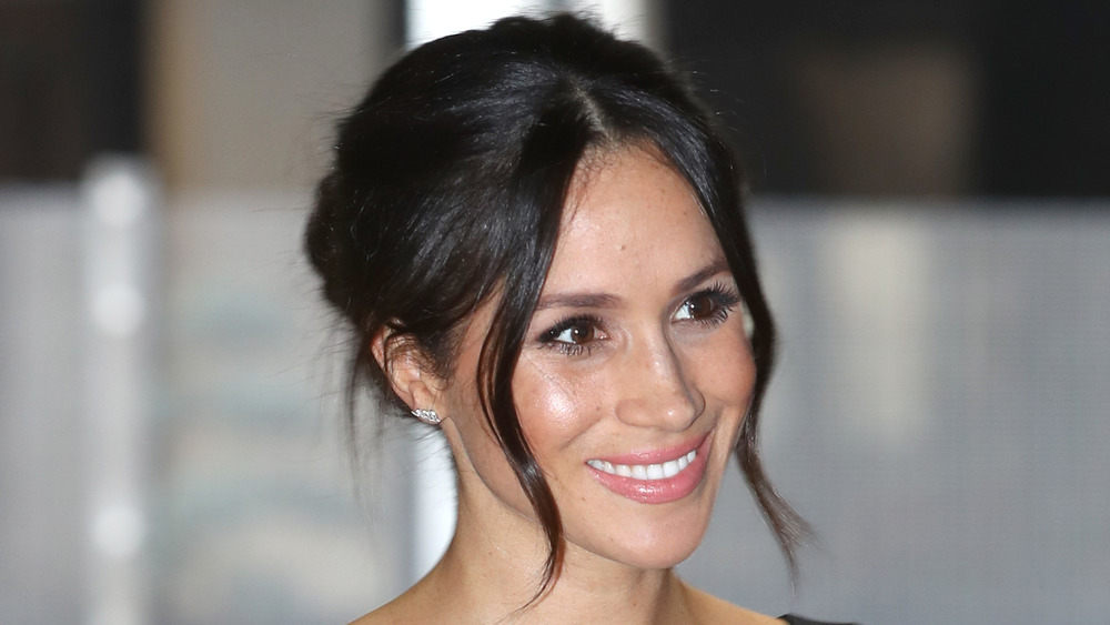 Meghan Markle souriant avec ses cheveux épinglés