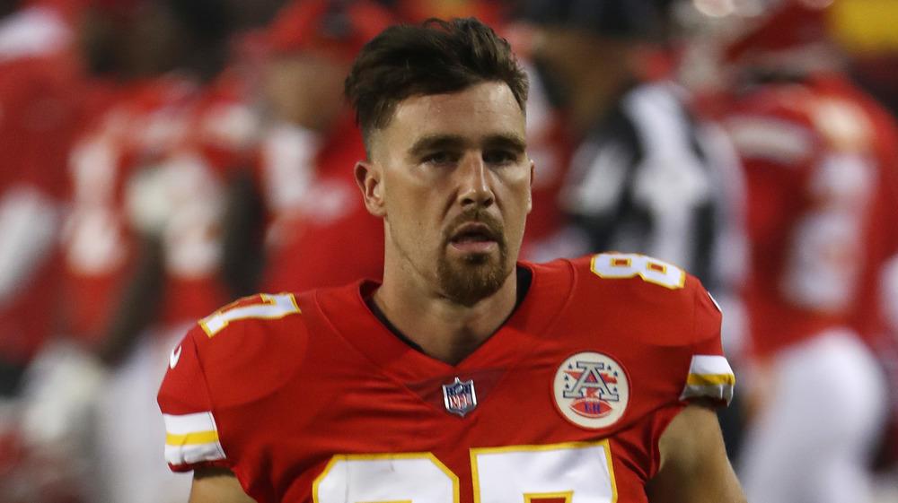 Travis Kelce, visage sérieux, en uniforme, sur le terrain, cheveux longs, barbiche