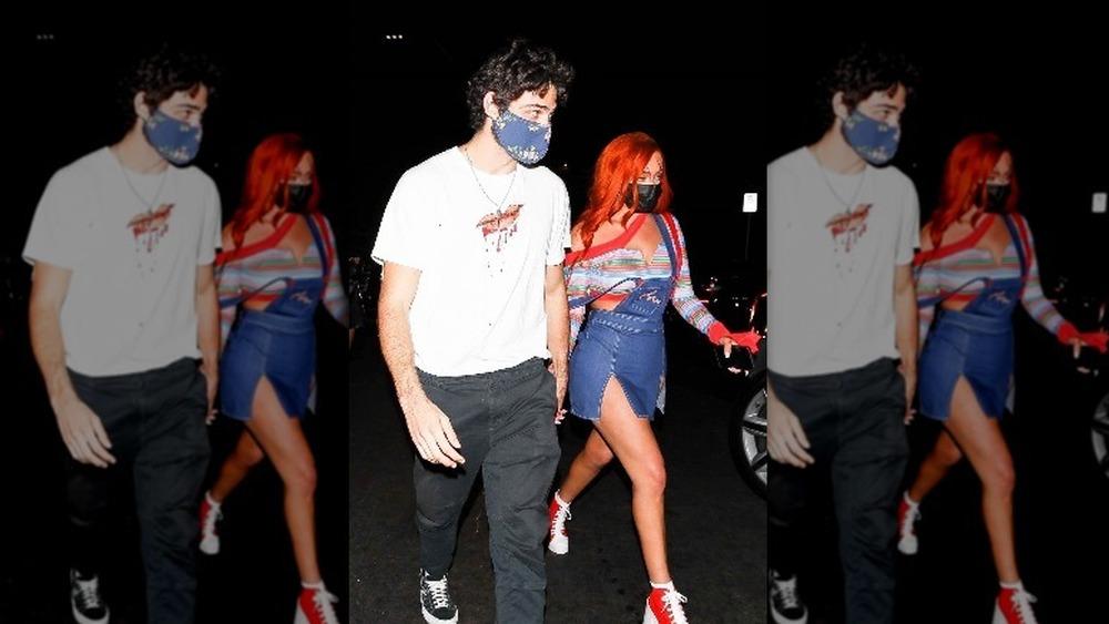 Noah Centineo et Stassie Karanikolaou se tenant la main lors d'une fête d'Halloween