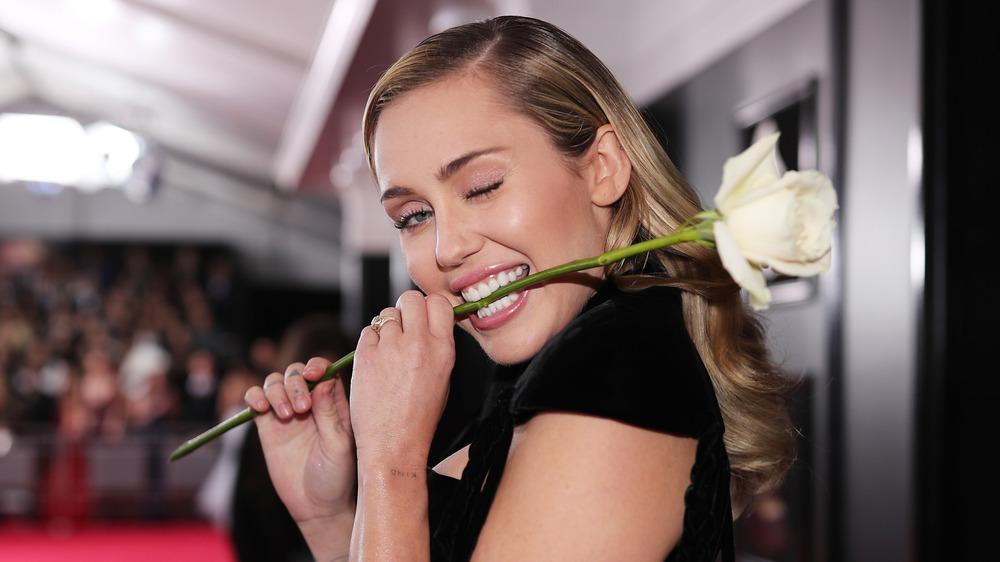 Miley Cyrus clignant de l'œil et mordant une tige de fleur