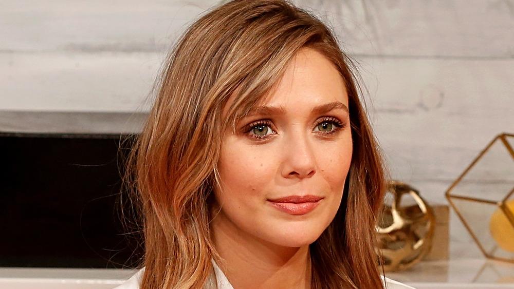 Elizabeth Olsen porte un chemisier blanc lors d'une interview