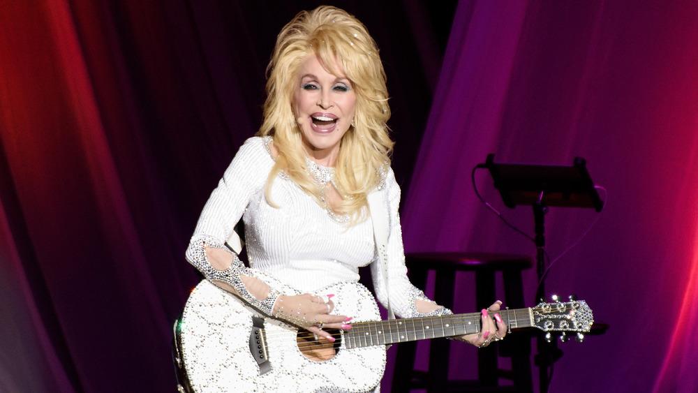 Dolly Parton jouant de la guitare sur scène