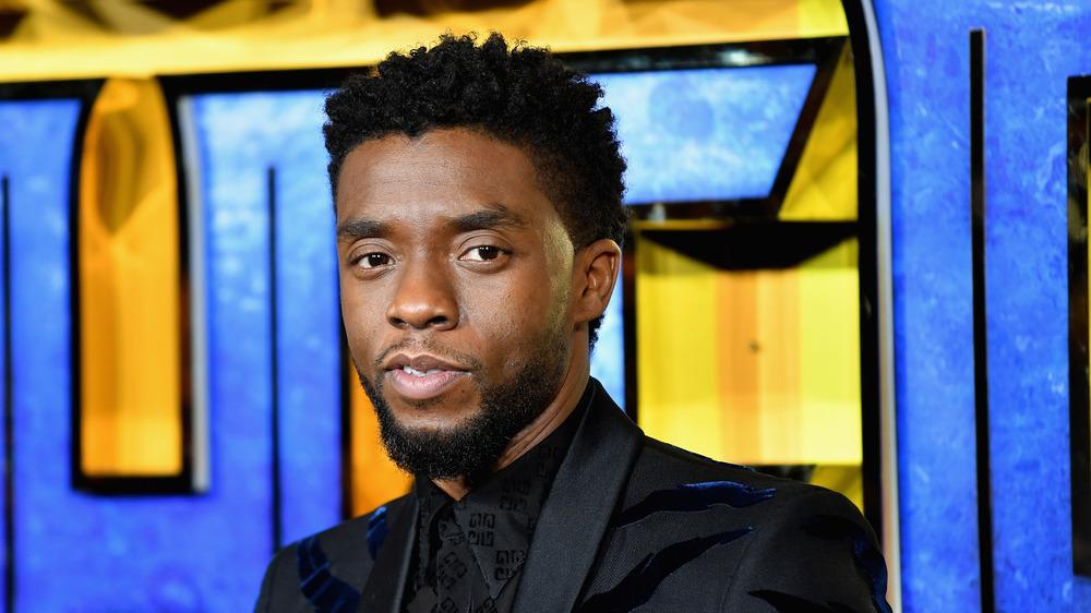 Chadwick Boseman posant un costume noir