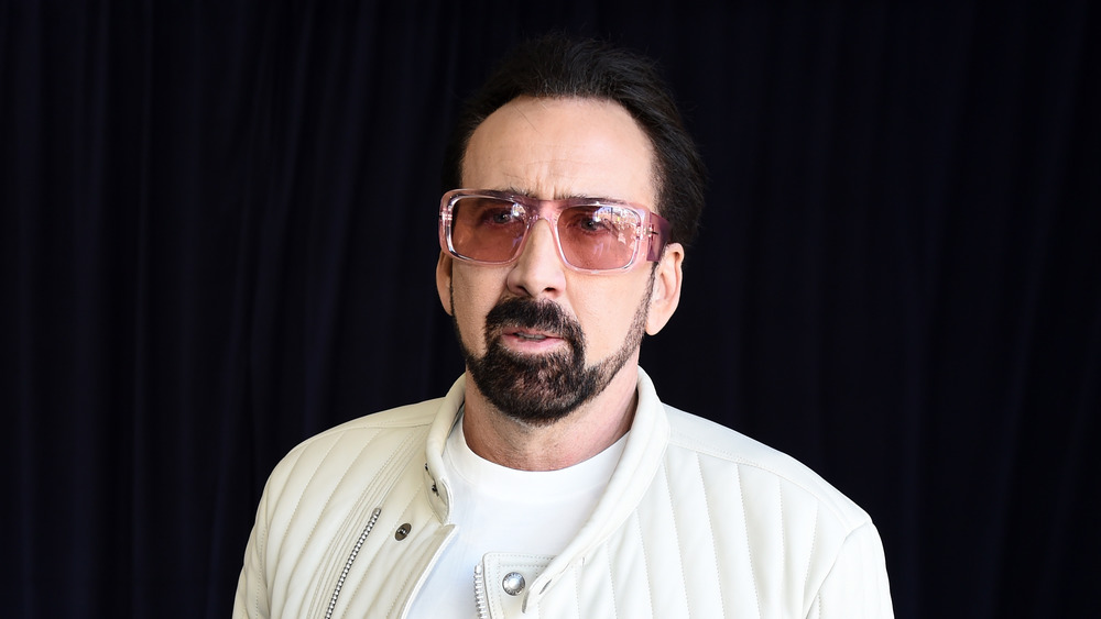 portrait de Nicolas Cage dans une veste blanche et des lunettes de soleil roses