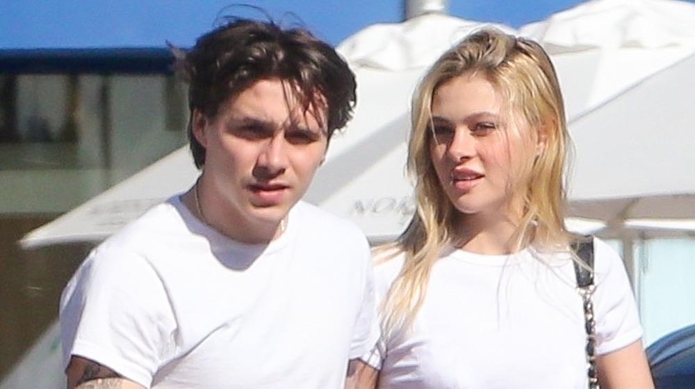 Brooklyn Beckham et Nicola Peltz portant des t-shirts blancs assortis, marchant dehors