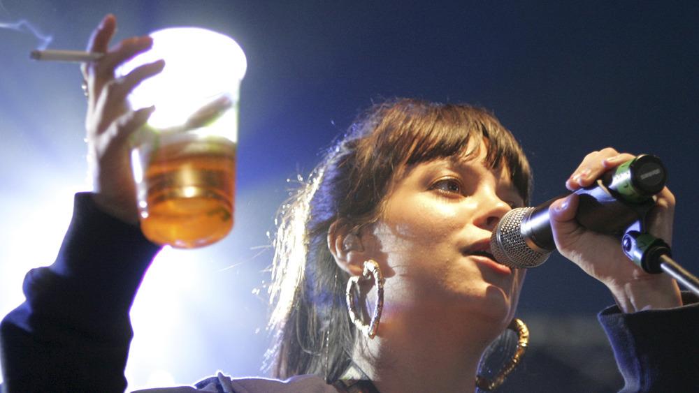 Lily Allen chante avec de la bière et une cigarette à la main
