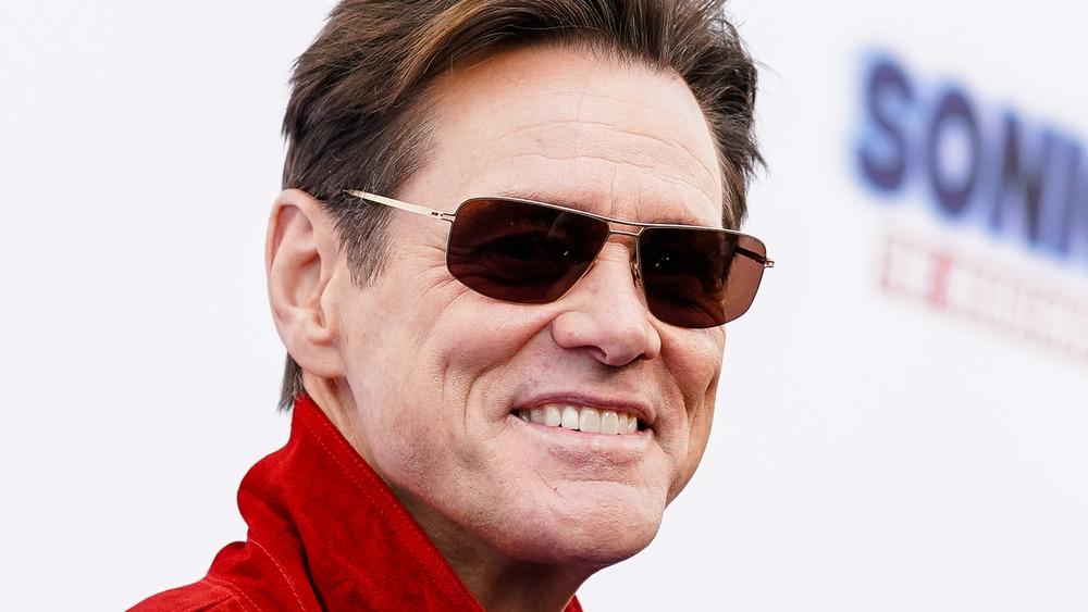 Jim Carrey portant des lunettes de soleil sur le tapis rouge
