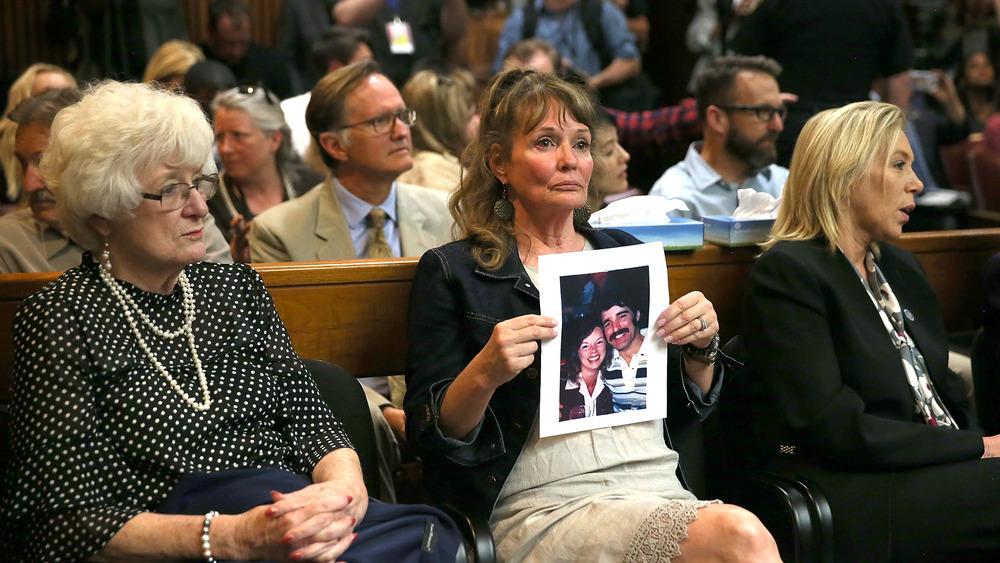 Un participant tient une photo des victimes Cheri Domingo et de son petit ami Gregory Sanchez