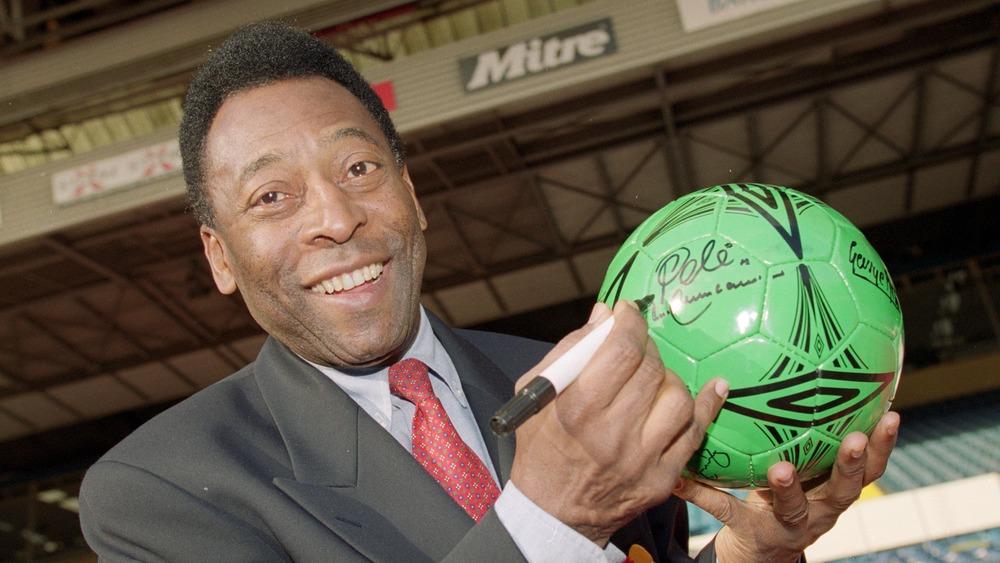 Pele signant un autographe sur un ballon de foot