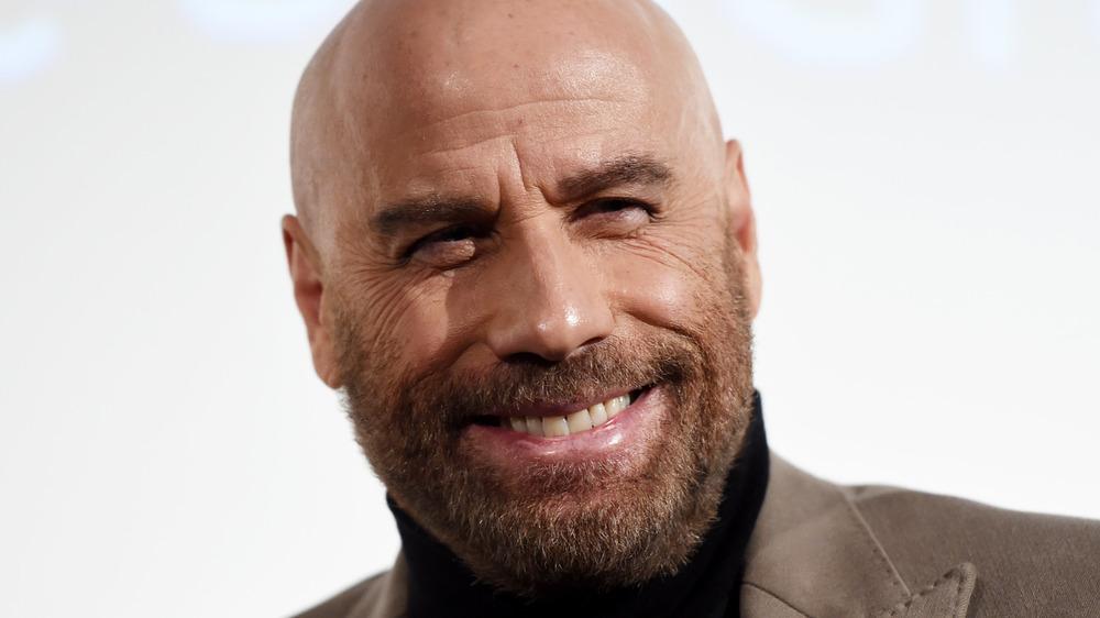 John Travolta sourit lors d'un événement sur le tapis rouge