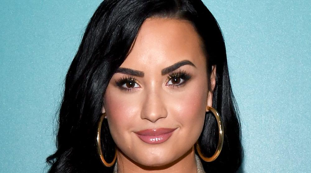 Demi Lovato souriant tout en portant des créoles