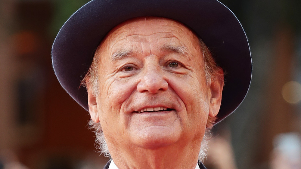 Bill Murray sourit portant un chapeau à bords bleu foncé