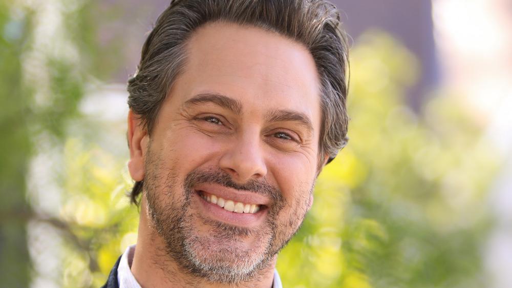 Thomas Sadoski, souriant, à l'extérieur, dans une chemise à col, poils du visage