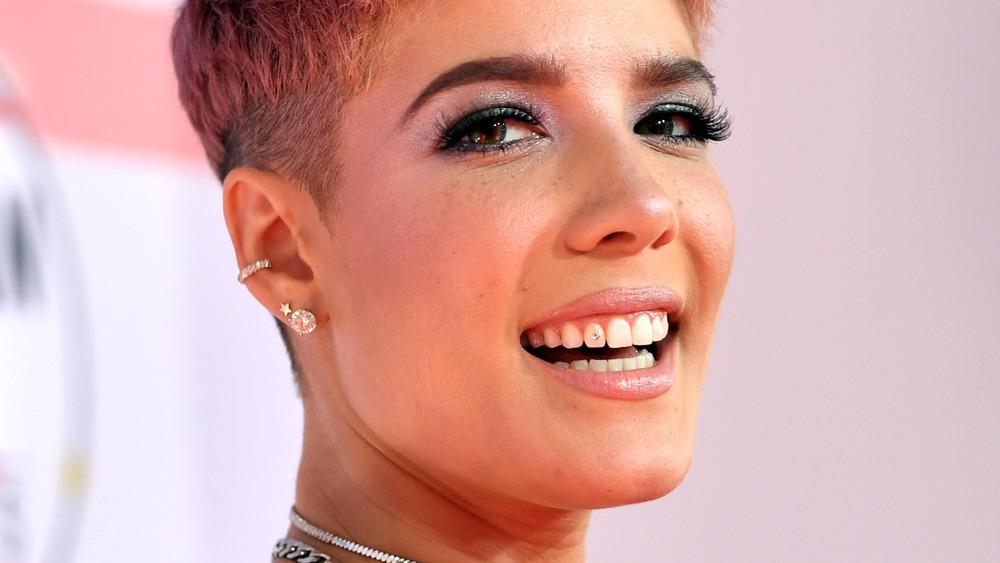 Halsey souriant avec un bijou sur sa dent