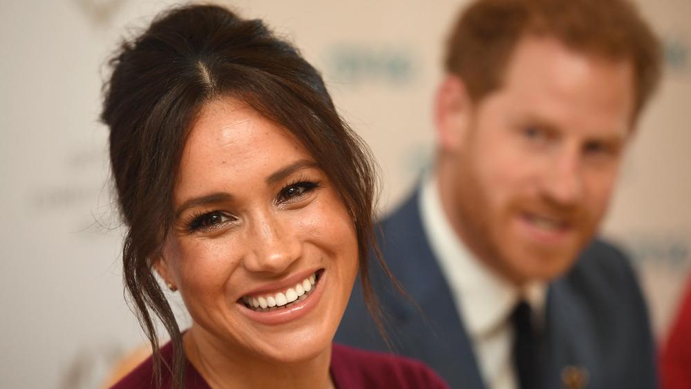 Meghan Markle souriant avec le prince Harry en arrière-plan