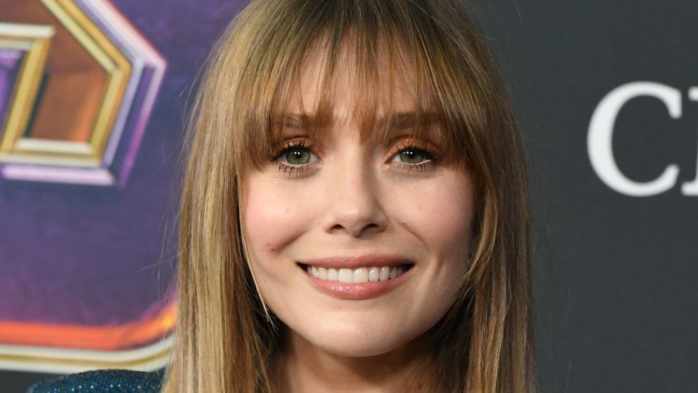 Elizabeth Olsen sourit en posant sur le tapis rouge