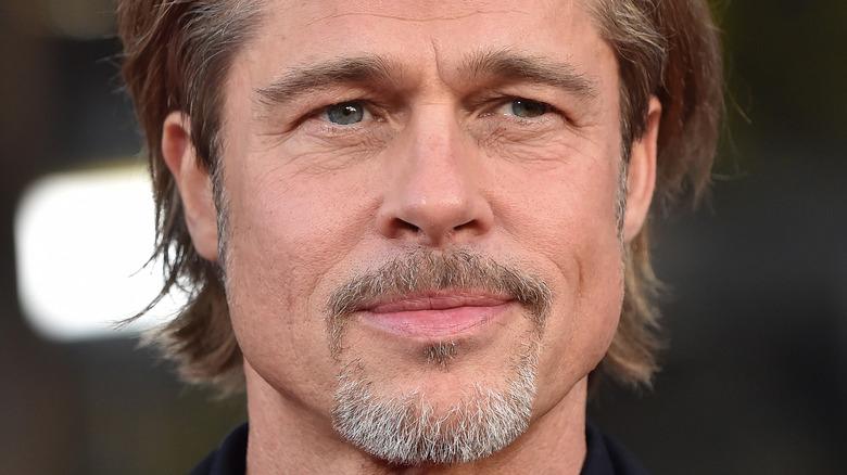 Brad Pitt arborant une barbe grisonnante et débraillée en souriant