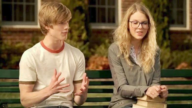 Lucas Till et Taylor Swift assis sur un banc