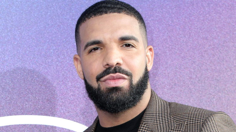 Drake regarde, vêtu d'un blazer à carreaux