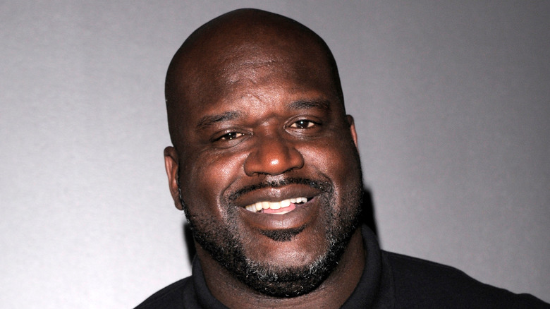 Shaquille O'Neal souriant dans un polo