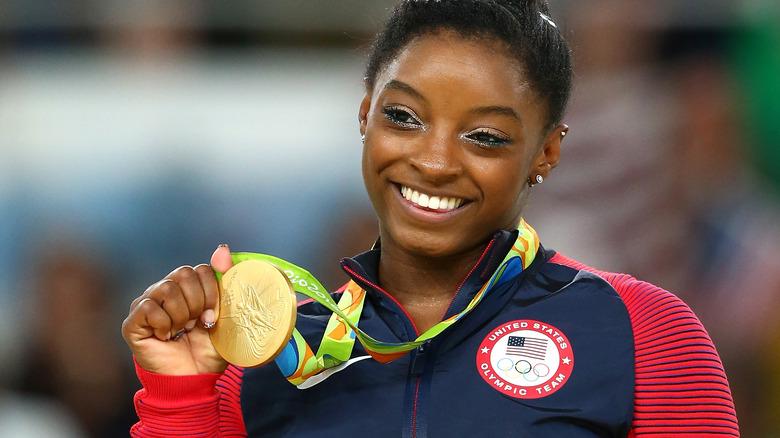 Simone Biles tenant la médaille