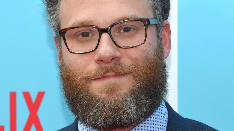 Seth Rogen pose en costume-cravate avec des lunettes.